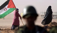 A Sahrawi woman holds a Polisario Front flag during a ceremony to mark 40 years since it proclaimed the Sahrawi Arab Democratic Republic. Photo by Getty Images.